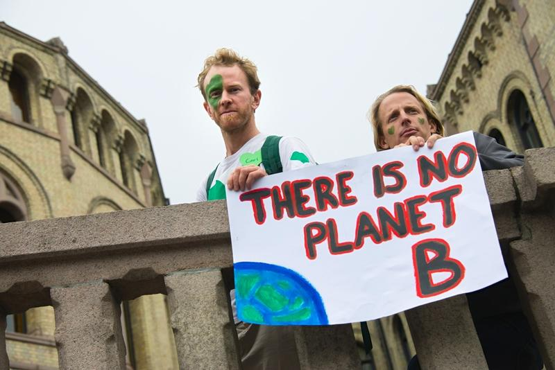 """Men hold a sign reading, """"There Is No Planet B"""", as thousands march through downtown Oslo, Norway, to support action on global climate change, September 21, 2014."""