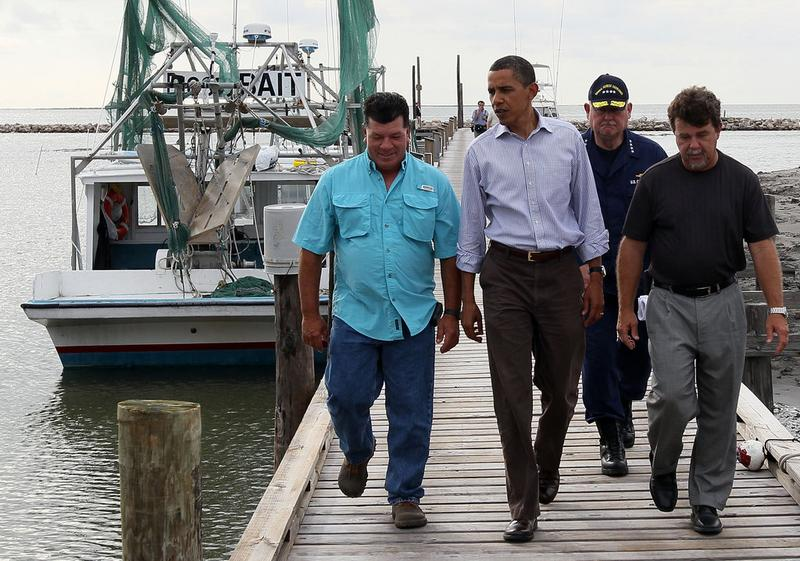 U.S. President Barack Obama is greeted by Mayor David Camardelle (R) of Grand Isle and Chris Camardelle (L) in Grand Isle, Louisiana, during his third visit to the state, June 4, 2010