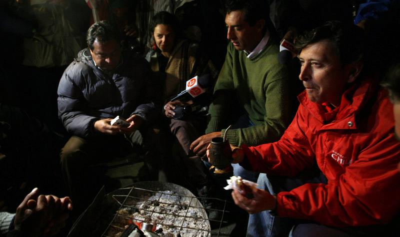 "Chilean Mining Minister Laurence Golborne (R) drinks ""mate"" -typical South American infusion- and eats with relatives of the miners trapped in San Jose mine near the city of Copiapo, on Oct 7, 2010."