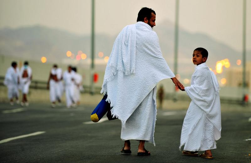 A Muslim pilgrim walks with his son along the road in the Mina valley three miles east of the Saudi Arabian holy city of Mecca during the Hajj, on November 14, 2010