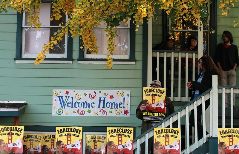 Occupy protesters stand on the steps of a foreclosed home that they re-occupied on December 6, 2011 in Oakland, California.