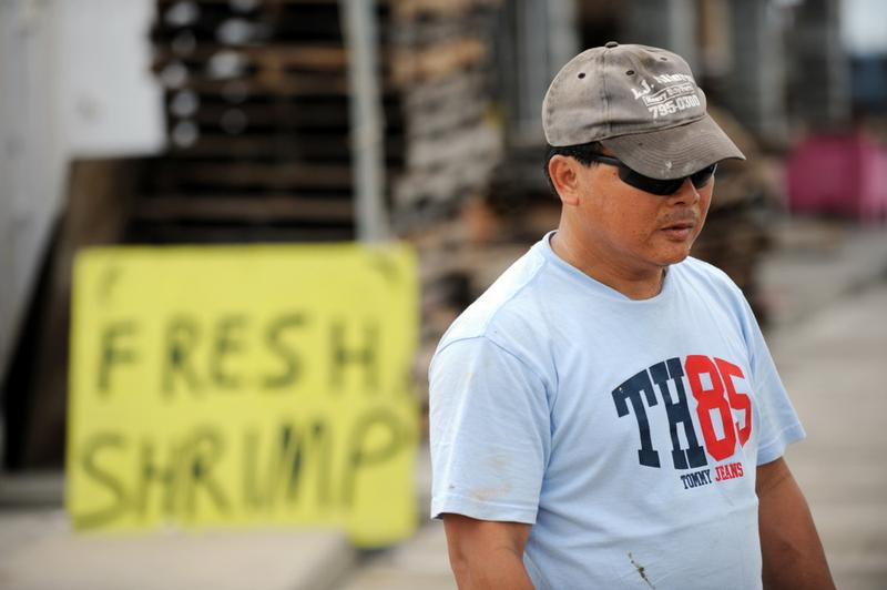 Boat owner Can Nguyen stand near a sign at a shrimp processor on a dock May 3, 2010 in Pass Christian, Miss., as he and the fleet are confined to port since the shutdown of all fishing on the Gulf.