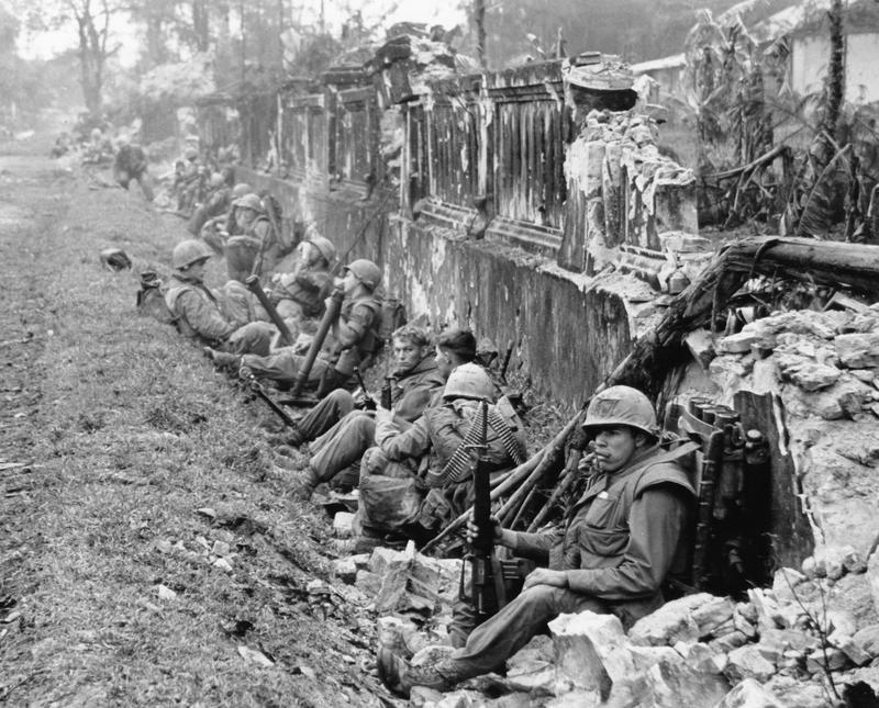 A unit of U.S. Marines rests alongside a battered wall of Hue's imperial palace after a battle for the Citadel in February 1968, during the Tet Offensive.