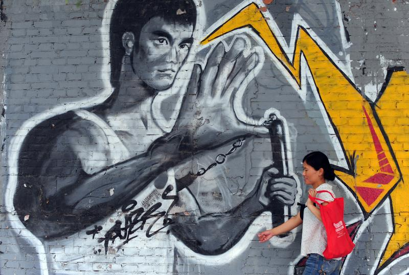 A woman walks past a mural of martial arts legend Bruce Lee painted along a graffiti-strewn wall in Beijing on July 22, 2010.
