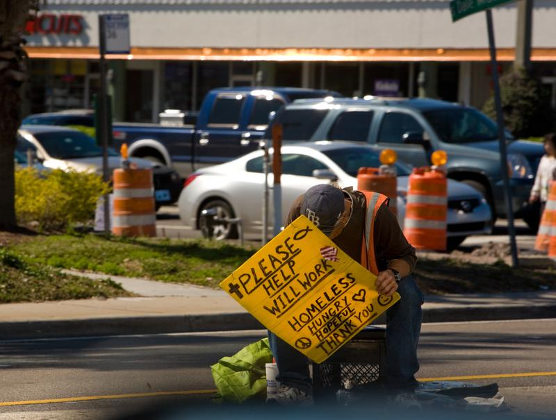 A homeless man sits along the Kennedy Blvd traffic island on February 14, 2011 in Tampa, Florida.