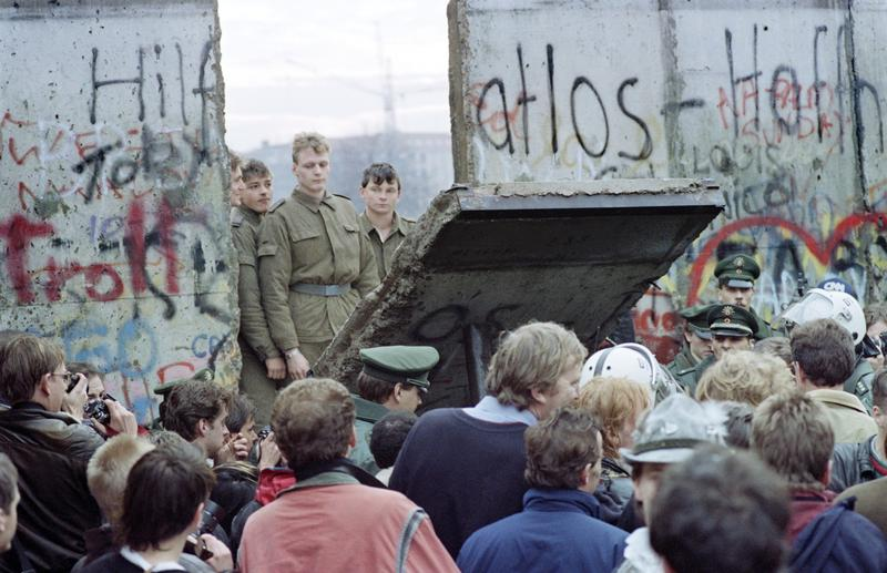 West Berliners crowd in front of the Berlin Wall on Nov. 11, 1989 as they watch East German border guards demolishing a section of the wall to open a new crossing point between East and West Berlin.