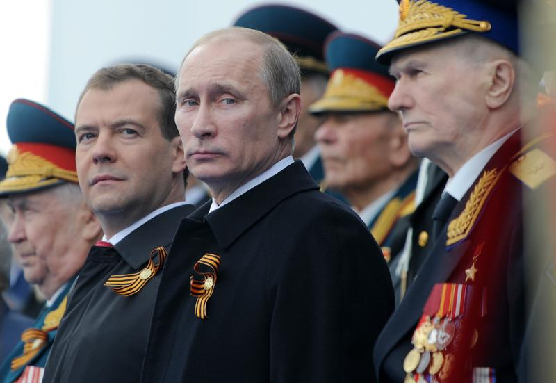 Russian President Dmitry Medvedev (L), Prime Minister Vladimir Putin (2nd L) and WW II veterans watch a military parade during the nation's Victory Day celebrations in Moscow on May 9, 2011.