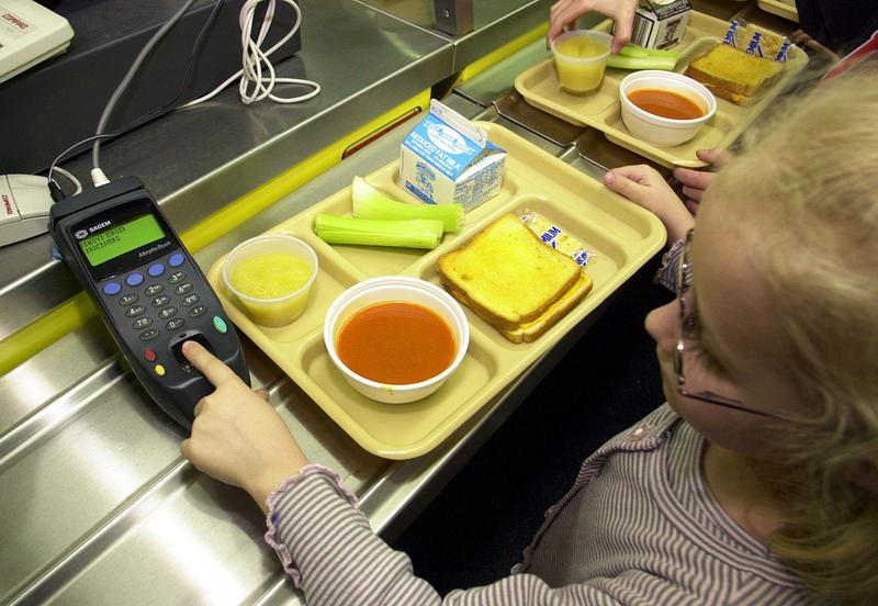 A student uses a fingerprint scanner to pay for lunch at an elementary school.