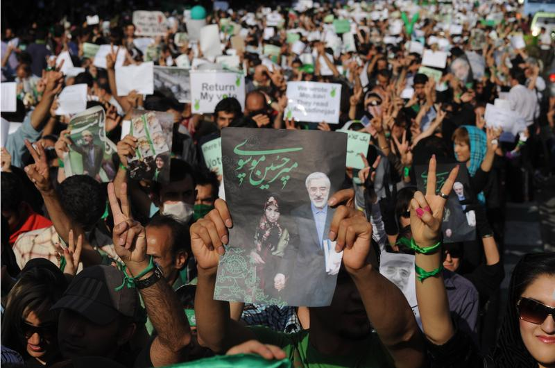 Demonstrators carry banners and pictures of Mir Hossein Mousavi, the defeated reformist candidate, during a march on Karimkhan Street, Tehran, 17th June 2009.