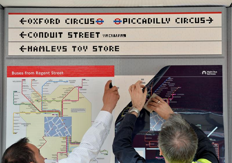 Putting the finishing touches on a London bus stop built entirely out of Lego.