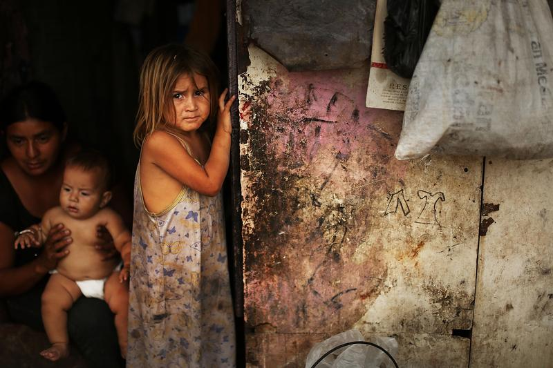 A child stands in the shack she shares with her family beside a dumpster in a gang infested neighborhood on July 17, 2012 in Tegucigalpa, Honduras.
