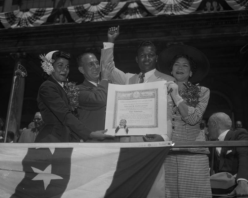 Mayor Vincent Impellitteri waves Sugar Ray Robinson arm aloft at City Hall while his wife, Edna Mae (left) and mom hold the scroll.