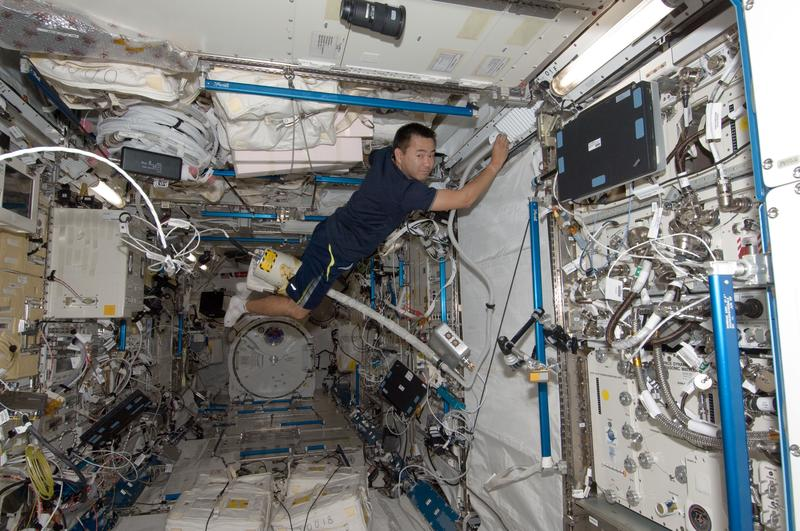 Japan Aerospace Exploration Agency astronaut Aki Hoshide, uses a vacuum cleaner during housekeeping operations in the Kibo laboratory of the International Space Station  July 28, 2012 in Space.