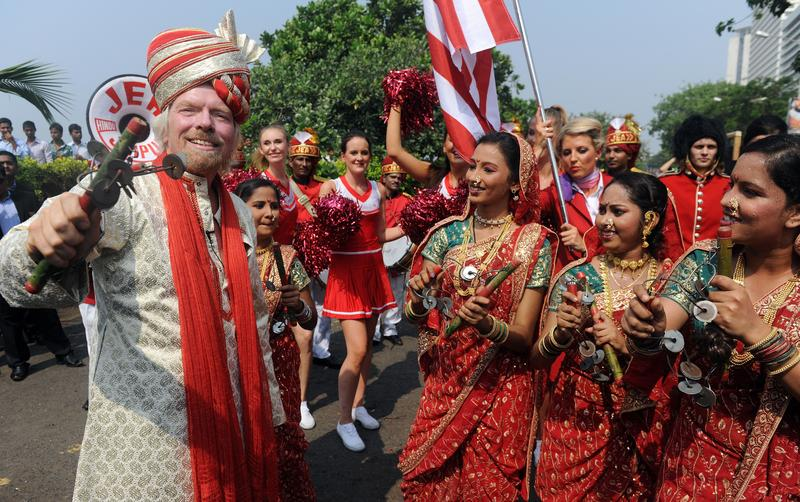 British business tycoon Richard Branson performs a traditional Lezim dance during a photo opportunity parade in Mumbai on October 26, 2012
