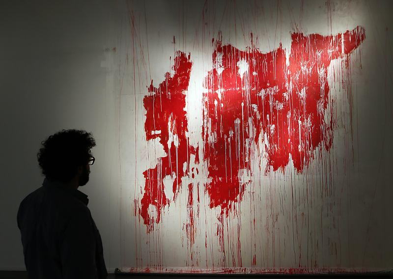 A man looks at a painting depicting a map of 'bleeding' war-torn Syria, part of an exhibition titled 'The Syrian Museum' on show in Dubai, on November 29, 2012.