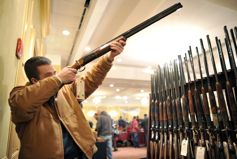 Collin McCarthy looks at a shotgun during the 8th Annual East Coast Fine Arms Show in Stamford, CT Jan. 6, 2013. This is the first gun show in Connecticut since the Sandy Hook shooting on 12/14/12.