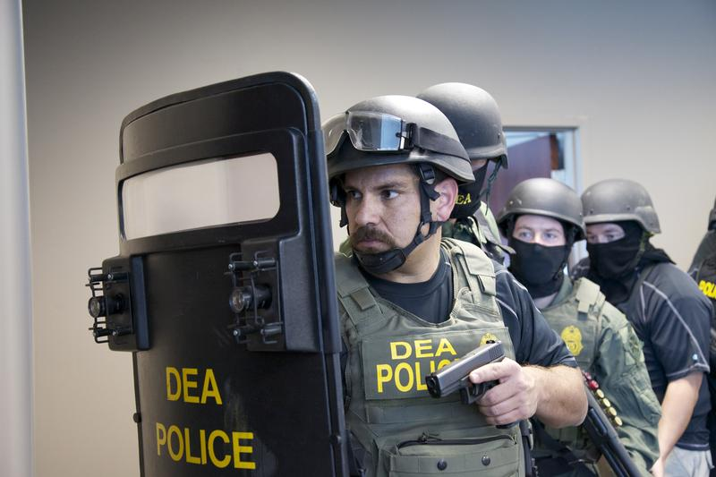 A group of Drug Enforcement Agency officers draw their weapons.
