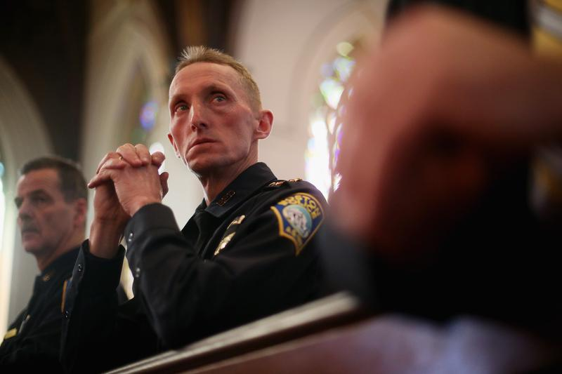 Then-Boston Police Department Superintendent William Evans (C) and Kevin Buckley (L) attend mass at the Cathedral of the Holy Cross on the first Sunday after the marathon bombings on April 21, 2013.