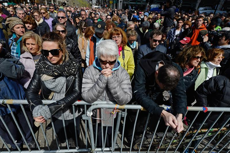 People hold a moment of silence near the Boston Marathon finish line on one week anniversary of the bombings on April 22, 2013 in Boston, MA.