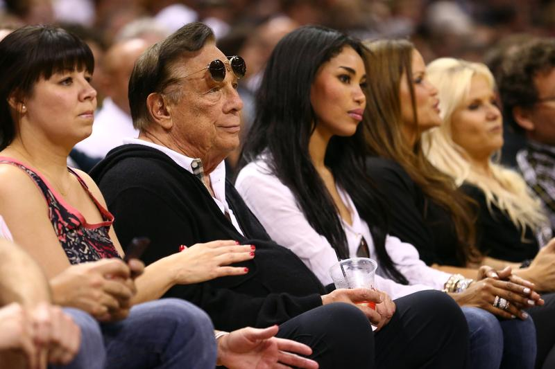 Donald Sterling, owner of the Los Angeles Clippers, sits next to his girlfriend V. Stiviano (R) during the 2013 NBA Playoffs at AT&T Center on May 19, 2013 in San Antonio, Texas.