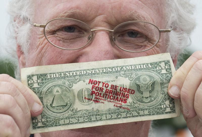 Ben Cohen, co-founder of Ben & Jerry's Ice Cream, holds up a one-dollar bill he stamped with the words 'Not to be used for bribing politicians' as he advocates to get money out of politics.