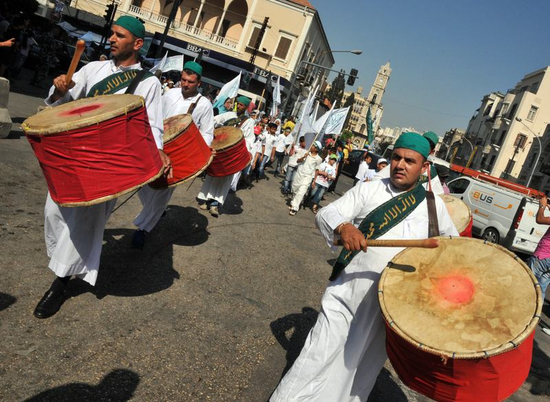 Sufi men parade, playing religious music, during a march prior to the start of Muslim holy fasting month of Ramadan in the streets of the northern Lebanese city of Tripoli on July, 8, 2013.