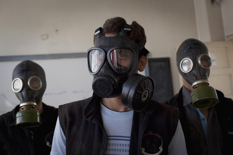 Volunteers wear gas masks during a class on how to respond to a chemical attack, in the northern Syrian city of Aleppo on September 15, 2013.