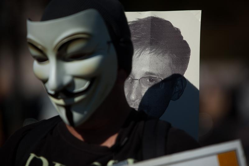 A protester wearing a mask marches with a sign featuring the likeness of former National Security Agency employee Edward Snowden during the Stop Watching Us Rally. October 26, 2013