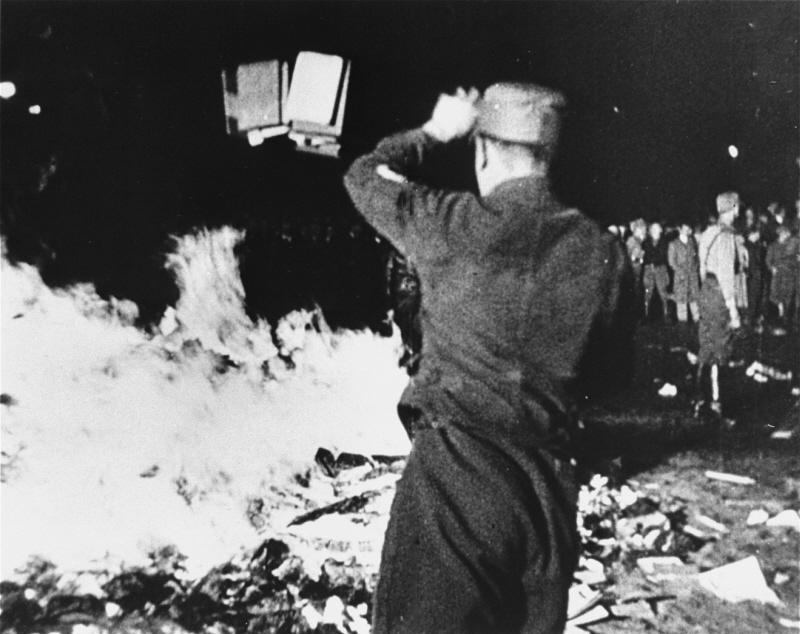 """A member of the SA throws confiscated books into the bonfire during the public burning of """"un-German"""" books in Berlin, May 10, 1933."""