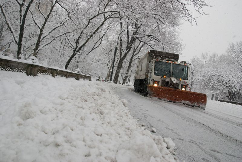 A snow plow driving through Central Park during an afternoon snowfall.