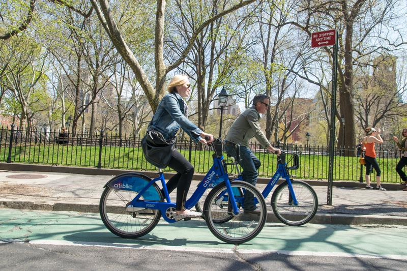 Cyclists ride Citi Bikes past Washington Square Park in late April.