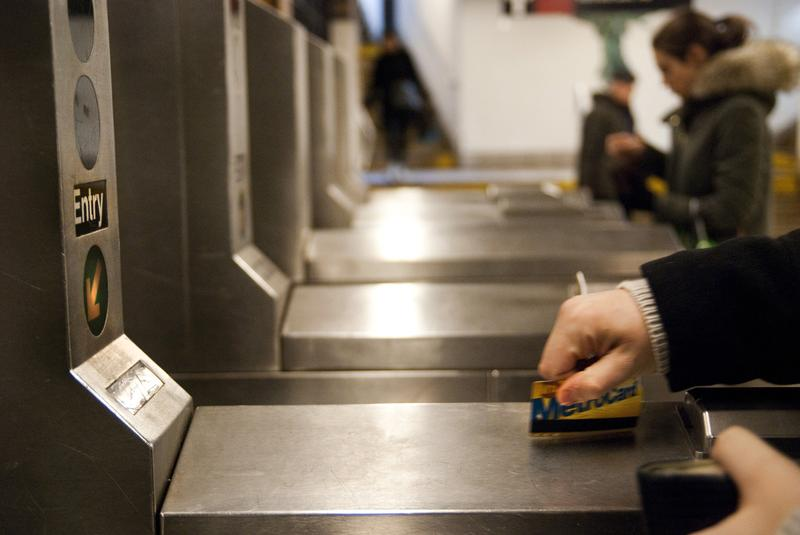 A commuter swipes their MTA metro card at a Brooklyn subway station.