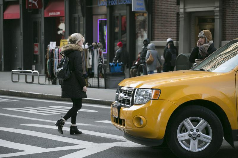 A cab and a pedestrian at a Manhattan crosswalk