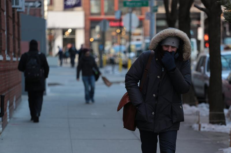 A man covers his face from the February chill in Greenwich Village.