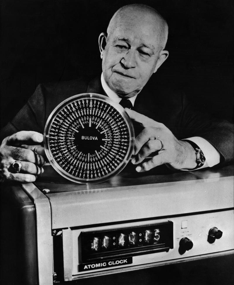 General Omar Bradley is showing a rock crystal clock produced by his company as well as an atomic clock, based on radiating alpha particles.