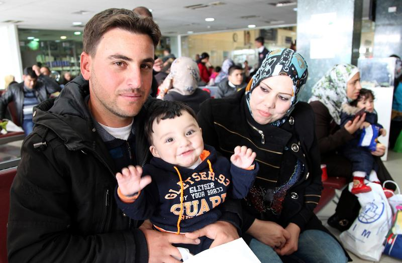 A Syrian family poses while waiting in an airport in Amman, Jordan, to board a plane to Canada where they will be resettled, Sunday, Dec. 2015.