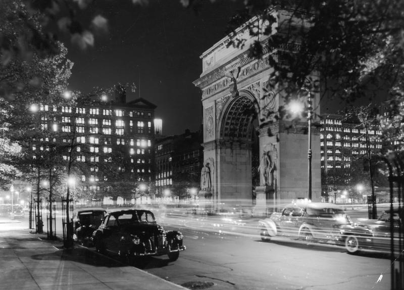circa 1945: View of the lights of cars at night in front of the Washington Arch in Washington Square Park, Greenwich Village, New York City