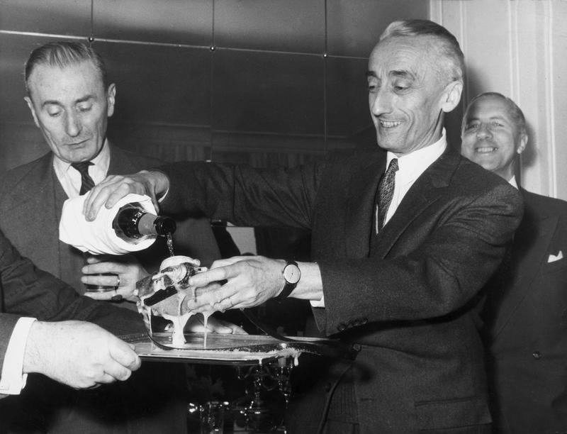 Jacques Cousteau (1910 - 1997) dousing a new type of underwater camera, the 'Calypso Phot,' with champagne at its unveiling ceremony, December 4, 1962.