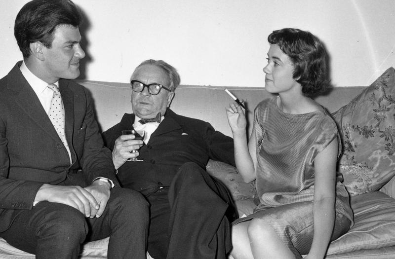 Raymond Chandler (1888 - 1959), centre, at a party in Portman Square, London. On either side of him are publisher Anthony Blond (1928 - 2008) and Blond's wife Charlotte.