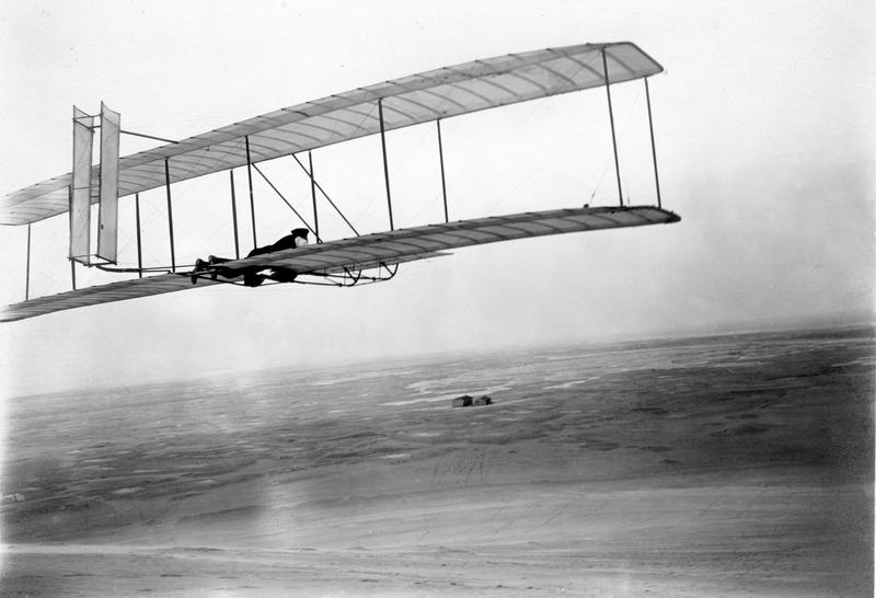 Wilbur takes wing in the 1902 glider soon after the brothers' return to Kitty Hawk in 1903. Their camp and shed stand alone in the distant wind-swept sands.