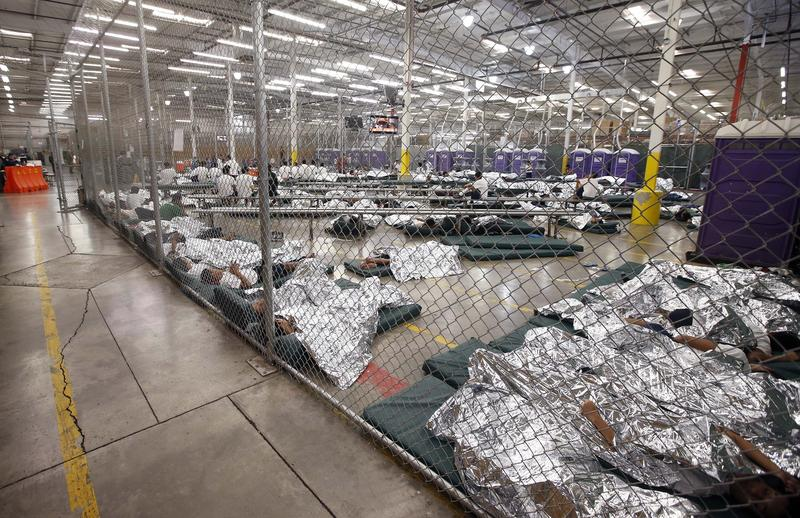 Detainees sleep and watch television in a holding cell where hundreds of immigrant children are being held at the U.S. Customs and Border Protection Nogales Placement Center. June 18, 2014