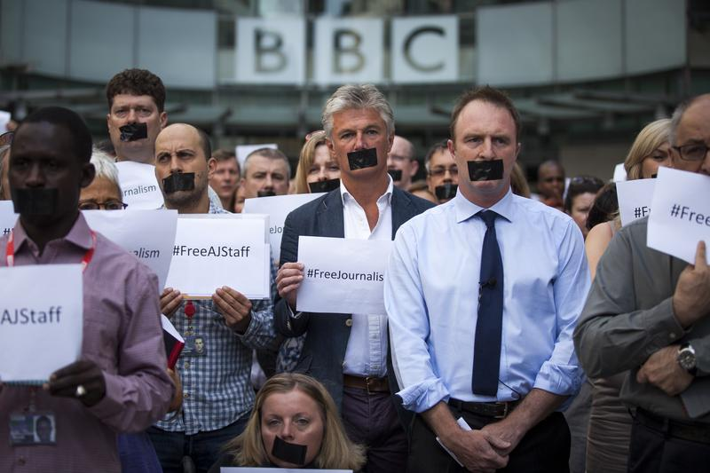 News organizations stage a one-minute silent protest outside New Broadcasting House against the seven-year jail terms given to three al-Jazeera journalists in Egypt on June 24, 2014 in London.