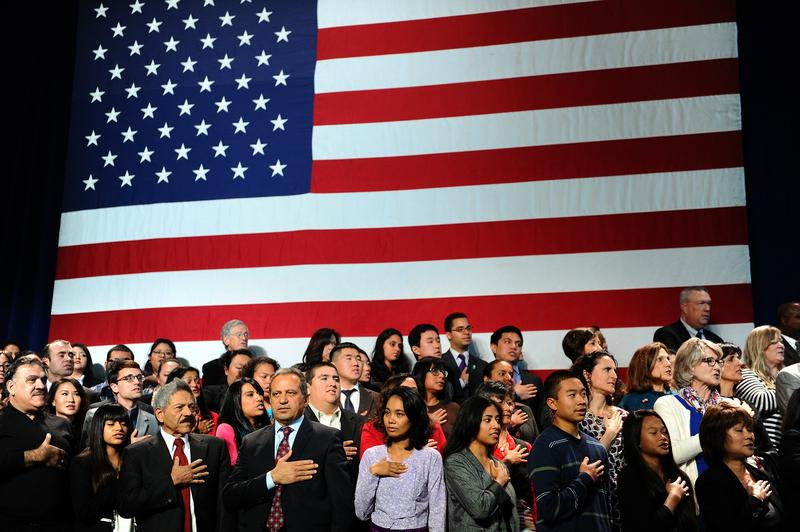Audience takes the pledge of allegiance before US President Barack Obama speaks on immigration reform at Betty Ann Ong Chinese Recreation Center in San Francisco, California, on November 25, 2013