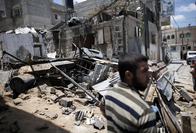 A Palestinian Hamas member stands guard in front of a destroyed building following an Israeli air strike on July 14, 2014 in Gaza City.