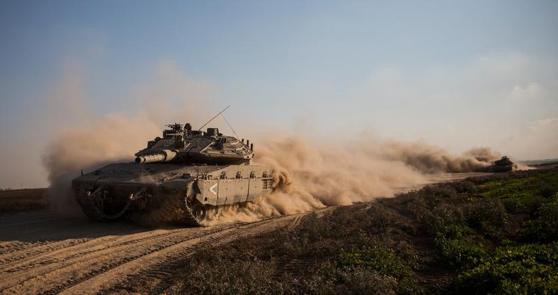 Israeli tanks change positions near the Israeli-Gaza border on July 23, 2014 near Kfar Aza, Israel. As operation 'Protective Edge ' enters its 16th day, 29 Israeli soldiers have been killed and over