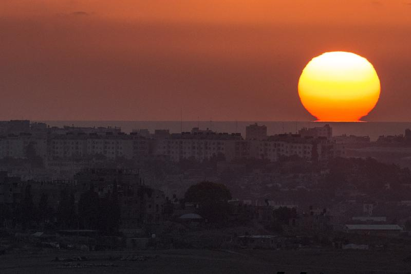 A picture taken from the southern Israeli Gaza border shows the sun setting over the Gaza strip
