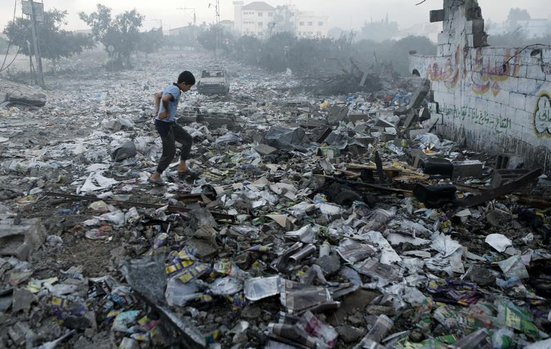 A Palestinian youth walks on debris as he inspects damages following an Israeli air strike in Gaza City, on July 24, 2014.