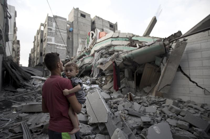 A Palestinian man carrying a child looks at the destroyed house of Hamas top leader in Gaza, Ismail Haniya, after it was hit by an overnight Israeli air strike, on July 29, 2014 in Gaza City.