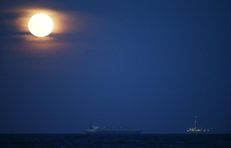 A supermoon rises in the sky above an oil platform and container ship on August 10, 2014 in Rio de Janeiro, Brazil.