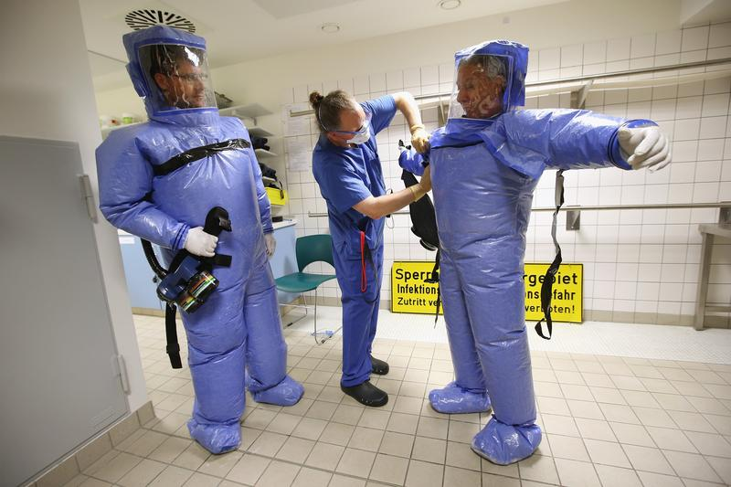 A nurse helps a doctor and nurse take off their isolation suits following a demonstration for the media of ebola treatment capabilities at Station 59 at Charite hospital on August 11, 2014 in Berlin.